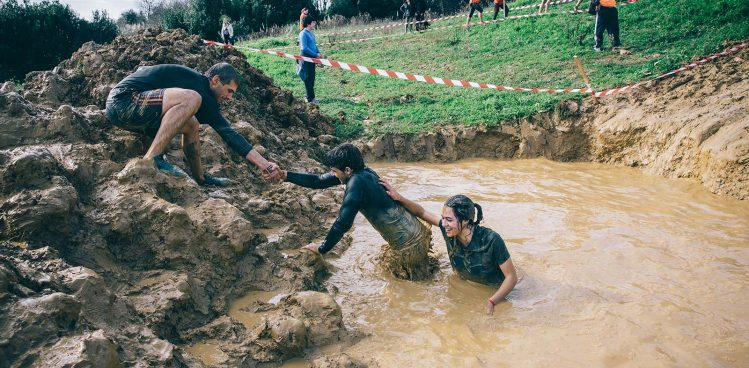 bigstock-Team-helping-to-cross-mud-pit-116872709.jpg